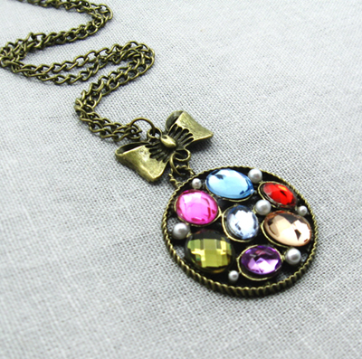 brass bow pendant necklace with rhinestones disc